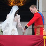 William takes Kate's hand on the balcony.