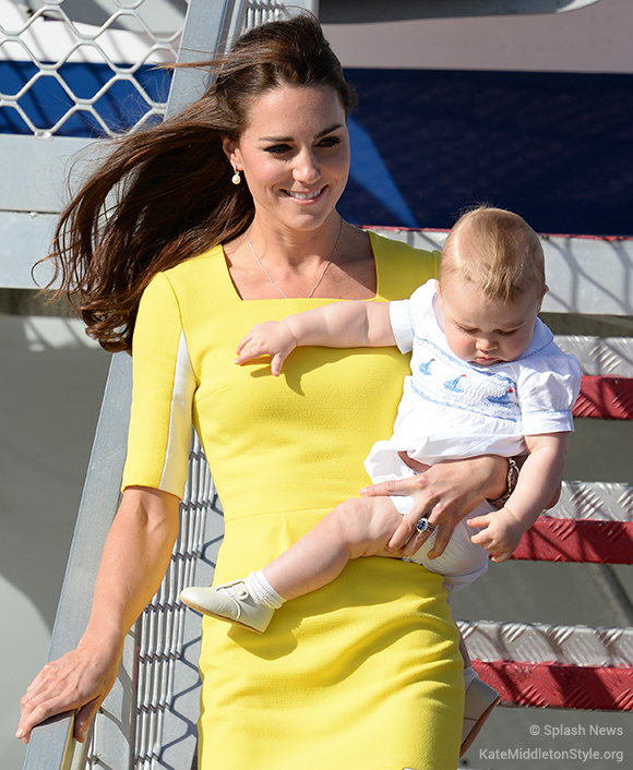 Kate stepping off the plane with baby George