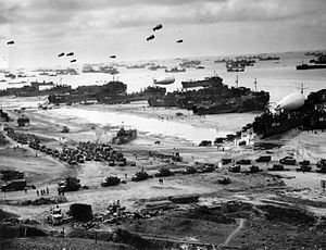 Tank landing ships unloading supplies on Omaha Beach, preparing for the break-out from Normandy © Wikimedia