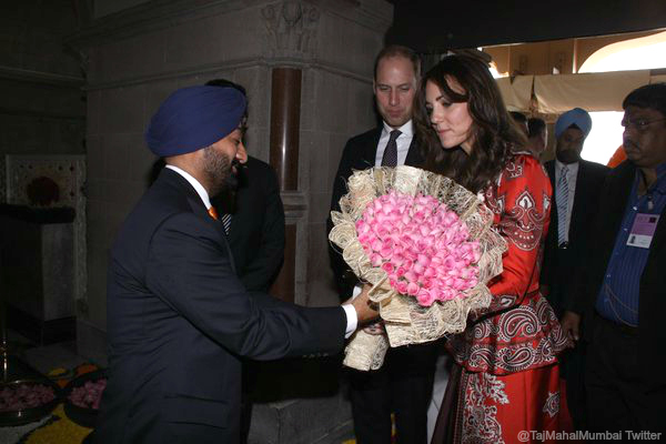 William and Kate are prestented with flowers at the Taj Palace