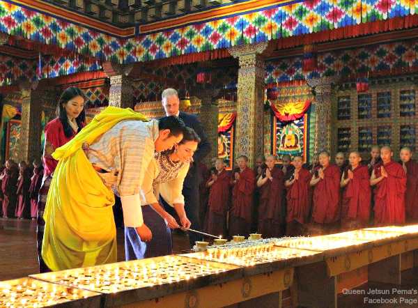 The two royal couples light butter lamps