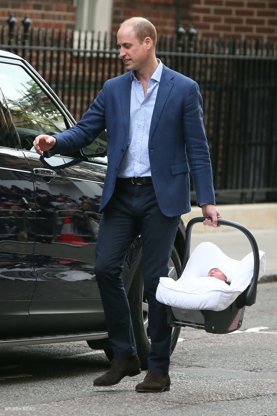 Prince William putting the new baby in the car