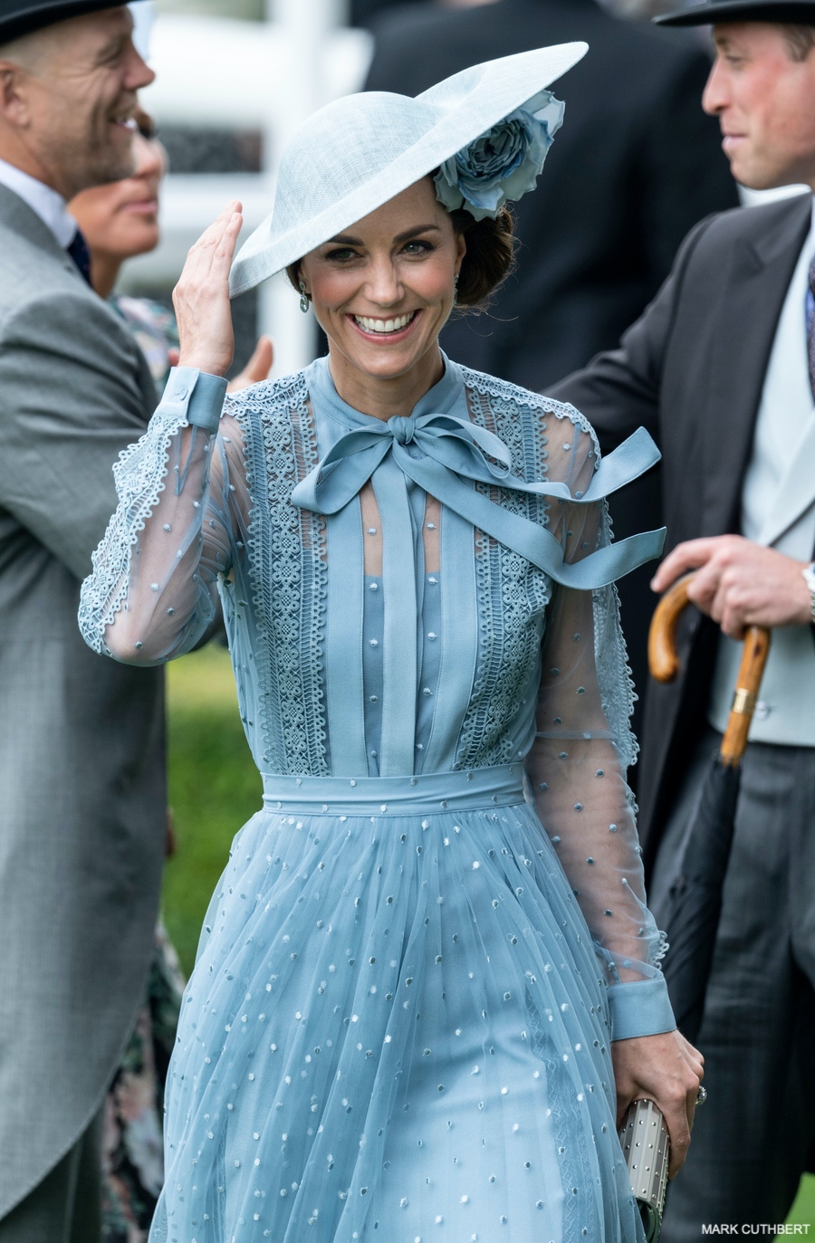 Kate Middleton wears blue ensemble at Royal Ascot 2019.  The Duchess appears slightly windswept as the bow on her dress blows in the wind.
