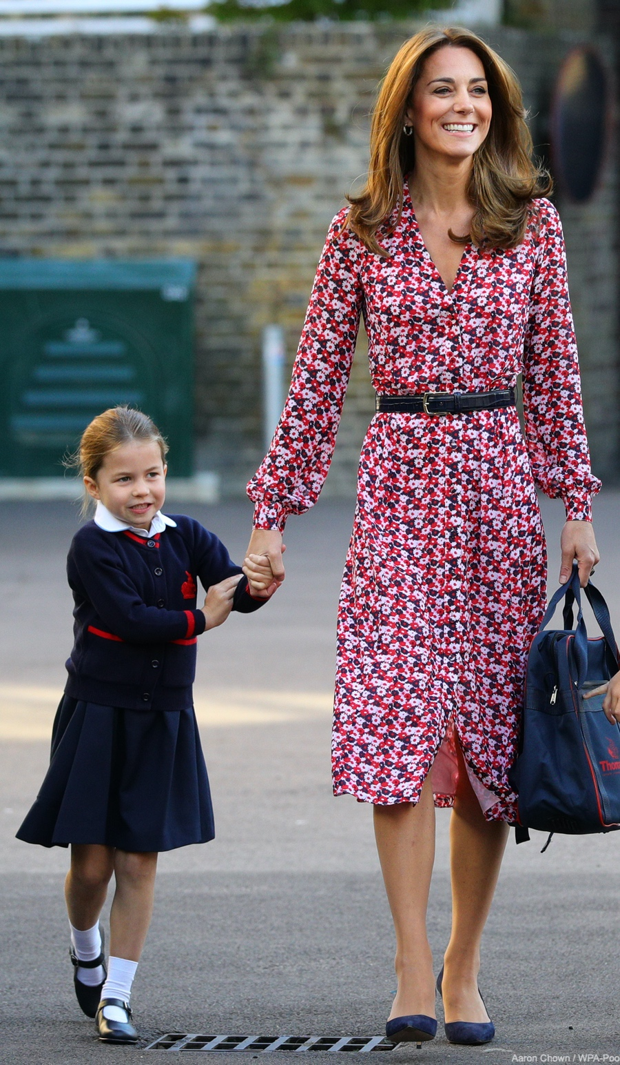 Kate Middleton takes Princess Charlotte to school for her first day. The Duchess is wearing a pink floral dress.